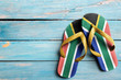canvas print picture - Thongs with flag of South Africa, on blue wooden boards