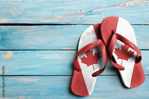 Spoed Foto op Canvas Canada Thongs with flag of Canada, on blue wooden boards