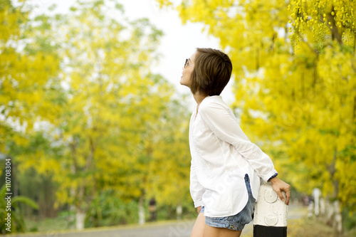 woman stand on the road full yellow flower