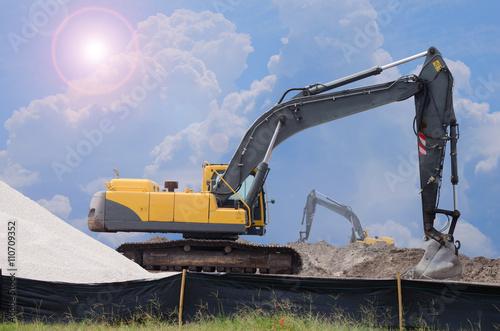 Fényképezés Bulldozers at work scooping dirt working at a construction site on a bright day with the sun bursting around the clouds