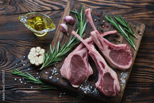 Photo  Rustic wooden chopping board with raw seasoned lamb steaks