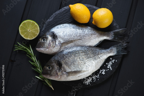 Fotografie, Obraz  Stone slate with raw dorados on a black wooden surface, top view