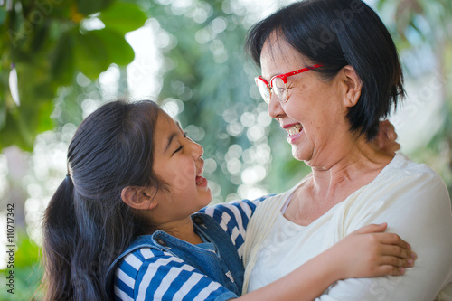 Fotografie, Obraz  Happy little Asian girl hugging her grandmother