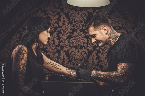 Professional tattoo artist makes a tattoo on a young girl's hand. Wallpaper Mural