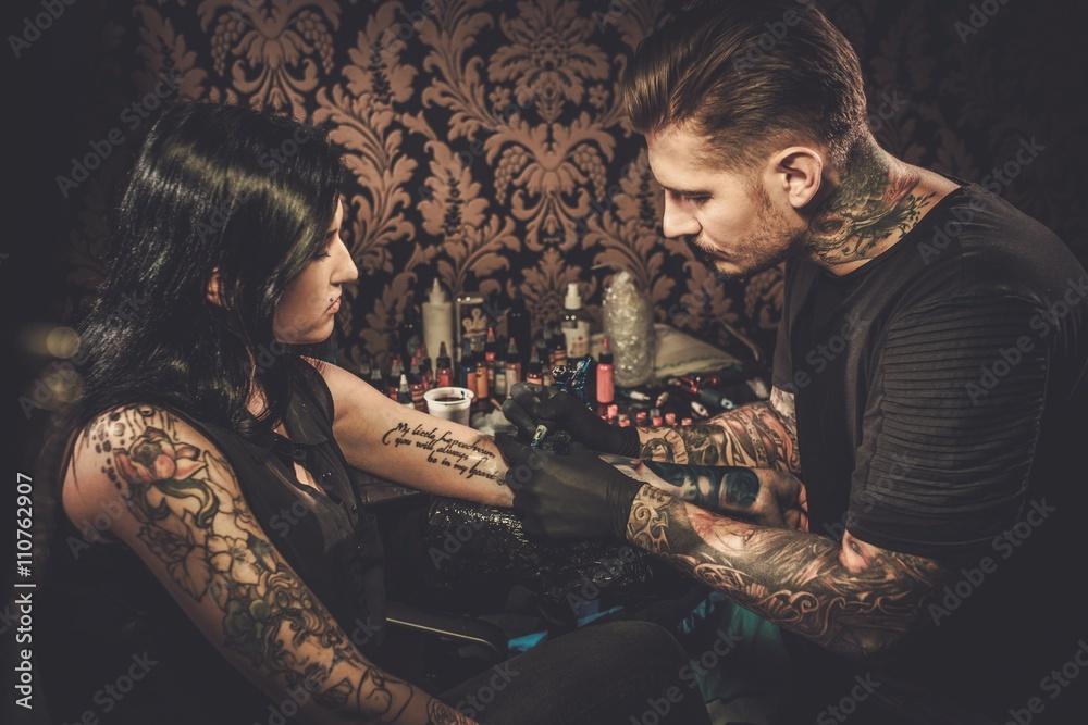 Fototapeta Professional tattoo artist makes a tattoo on a young girl's hand.