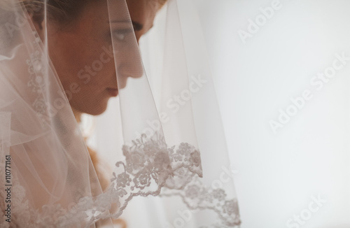 Obraz na płótnie Portrait of beautiful bride with fashion veil posing at home at wedding morning