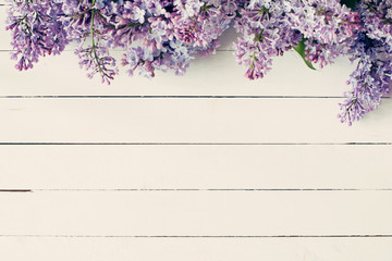 FototapetaLilac flowers on vintage wooden background. Top view, copy space