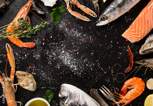 Poster Coquillage Fresh seafood on black stone.