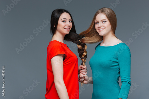 Fotografie, Obraz  Two happy young women made one brair with their hair