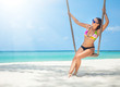 young woman in bikini and sunglasses on a swing on the shore of