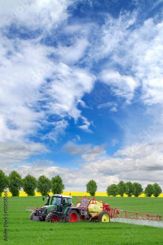 Photo  Konventionelle Landwirtschaft: Traktor mit Feldspitze sprüht Pflanzenschutzmitte