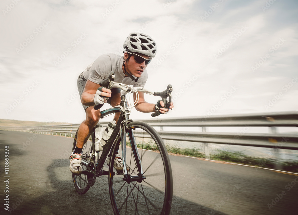 Fototapeta Cyclist pedaling on a racing bike outdoor