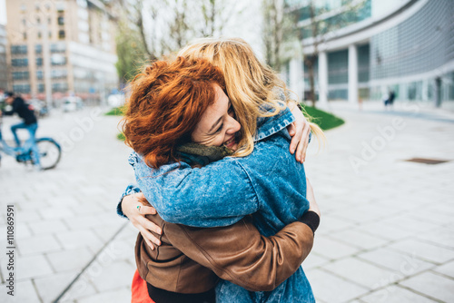 Two friends redhead and blonde girl meeting in the street of the city and huggin Fototapet