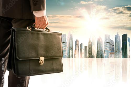 Fotografía  El hombre de negocios con la maleta contra la ciudad moderna