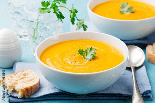 Pumpkin and carrot soup with cream and parsley on blue stone background Fototapet