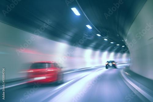 Plakat Tunel niebezpieczny wysokiej prędkości ruchu niewyraźne jazdy pojazdu. Zastosowano filtr koloru niebieskiego. Rozmycie ruchu wizualizuje prędkość i dynamikę.