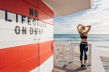 Young Woman On Lifeguard Platform, Looking At View, Rear View
