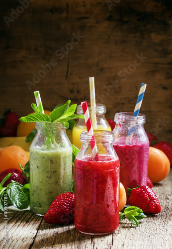 obraz dibond Multi-colored bottles with fresh fruit smoothies with striped st