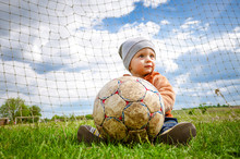 The Baby In A Cap Plays With A Ball