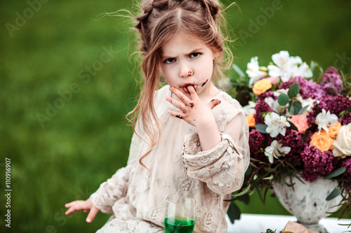 Little baby girl eats chocolate cake in nature at a picnic Poster