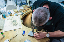 Jewellery Craftsman Using Hammer On Workbench