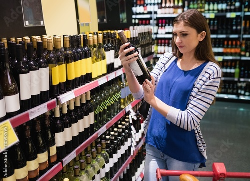 Woman looking at wine bottle Canvas Print