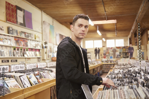 Poster Muziekwinkel Young man browsing vinyl records in music store