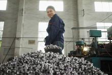 Worker Shovelling Metal Compon...