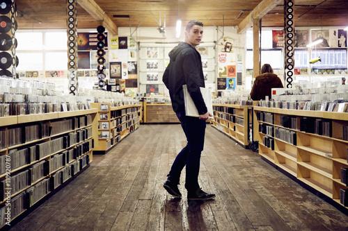 Spoed Foto op Canvas Muziekwinkel Young man holding vinyl record in music store