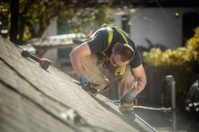 Solar Panel Installation Worker Working On Roof Of House