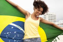 Portrait Of Young Woman Dancing With Brazilian Flag On Ipanema Beach, Rio De Janeiro, Brazil