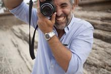 Portrait Of Male Photographer Using Digital SLR Camera, Ipanema Beach, Rio De Janeiro, Brazil