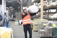 Young Male Warehouse Worker Carrying Polystyrene Roll On Shoulder