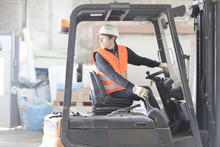 Young Male Warehouse Worker Reversing Forklift Truck In Warehouse