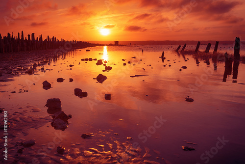 Poster Bordeaux Beautiful sunny red sunset on the lake with stones, wooden posts and reflection, natural seasonal summer vacation background