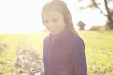 Smiling Girl Wearing Headphones Metal Detecting  In Field