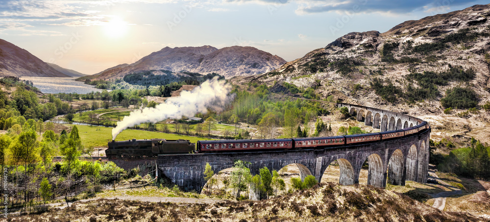 Fototapeta Glenfinnan Railway Viaduct in Scotland with the Jacobite steam train against sunset over lake