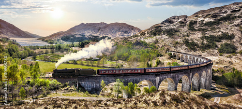 Fotografie, Obraz Glenfinnan Railway Viaduct in Scotland with the Jacobite steam train against sun