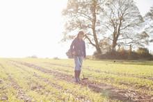 Girl Wearing Headphones Using Metal Detector In Sunlit Field
