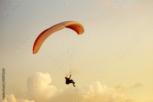 Deurstickers Luchtsport Paraglider flies on clouds backdrop