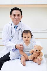 Portrait of smiling Vietnamese doctor hugging cute little baby