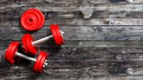 3D rendering of adjustable metallic red dumbbells, on wooden background with copy-space