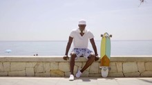 Skater Seated On Stone Wall By Ocean On Sunny Day While Wearing Hawaiian Shorts And White Cap And With Headset Around His Neck