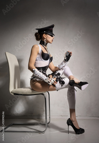 Stampa su Tela  Girl in a very fashionable lingerie and cap, sitting on a chair