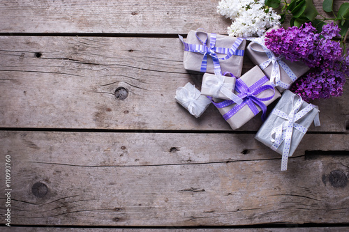 Wrapped gift boxes with presents and lilak flowers on aged woo