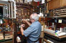 Senior Man Selecting Tools In Traditional Bookbinding Workshop
