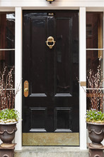 Black Front Door, With Planters And A Brass Door Knocker