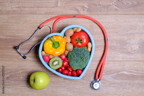 Fotografie, Obraz  Heart shaped dish with vegetables and stethoscope isolated on wooden background
