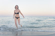 Mid adult woman running and splashing in sea, Sardinia, Italy