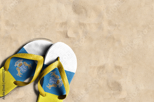 Deurstickers Canarische Eilanden Thongs with flag of Canary Islands, on beach sand